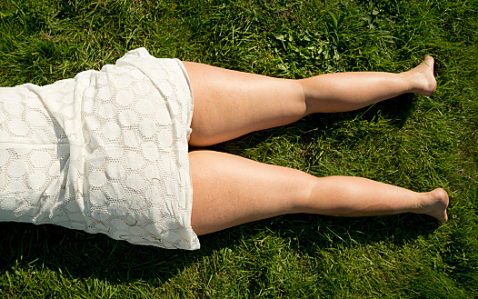 Womans legs laying in grass